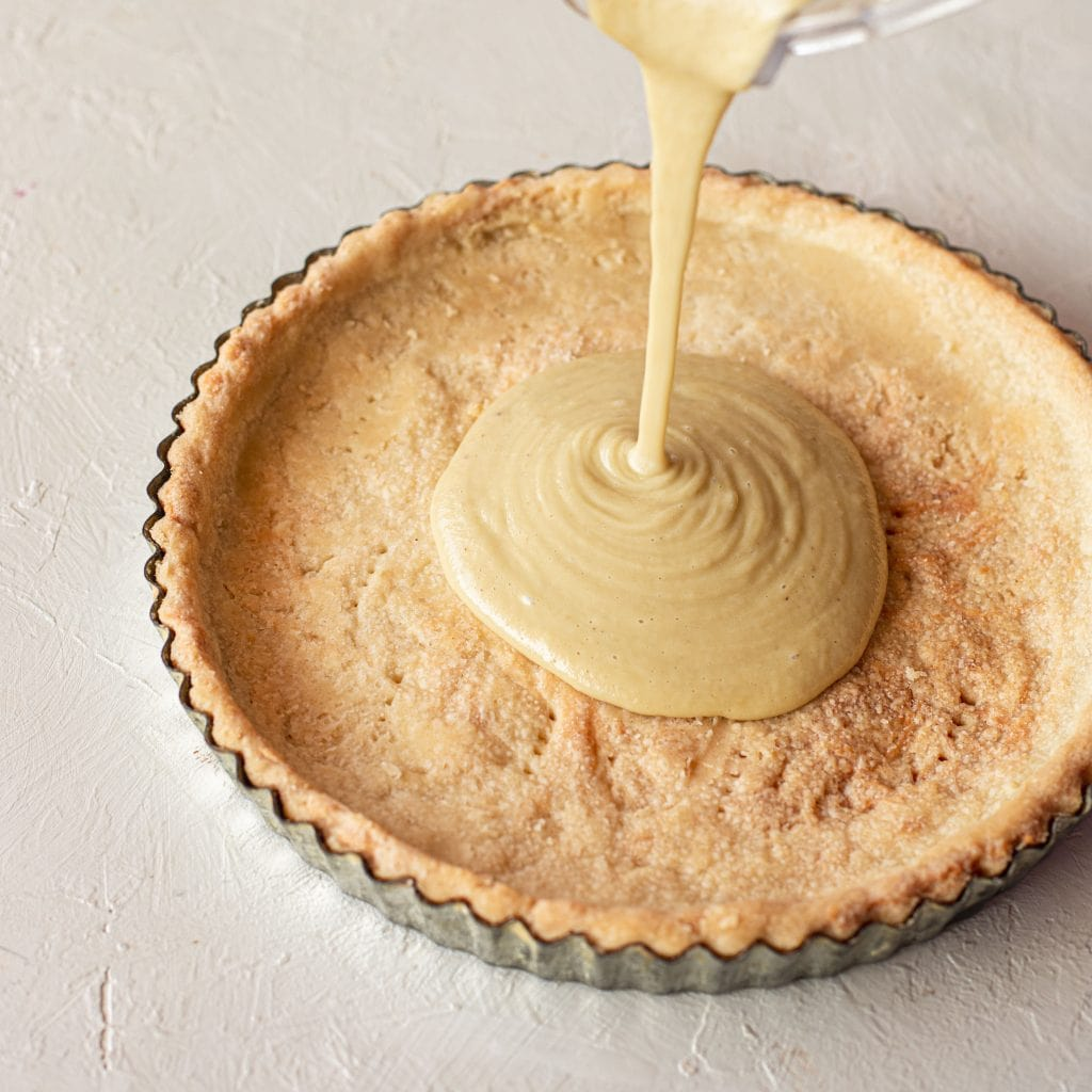 Image of cashew cream being poured into a baked shortcrust pastry shell