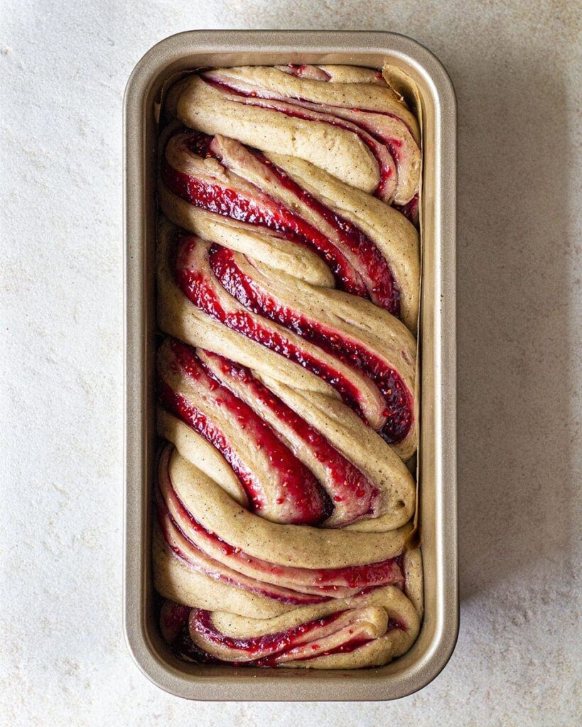 Unbaked raspberry jam donut babka in long baking tin after second proof