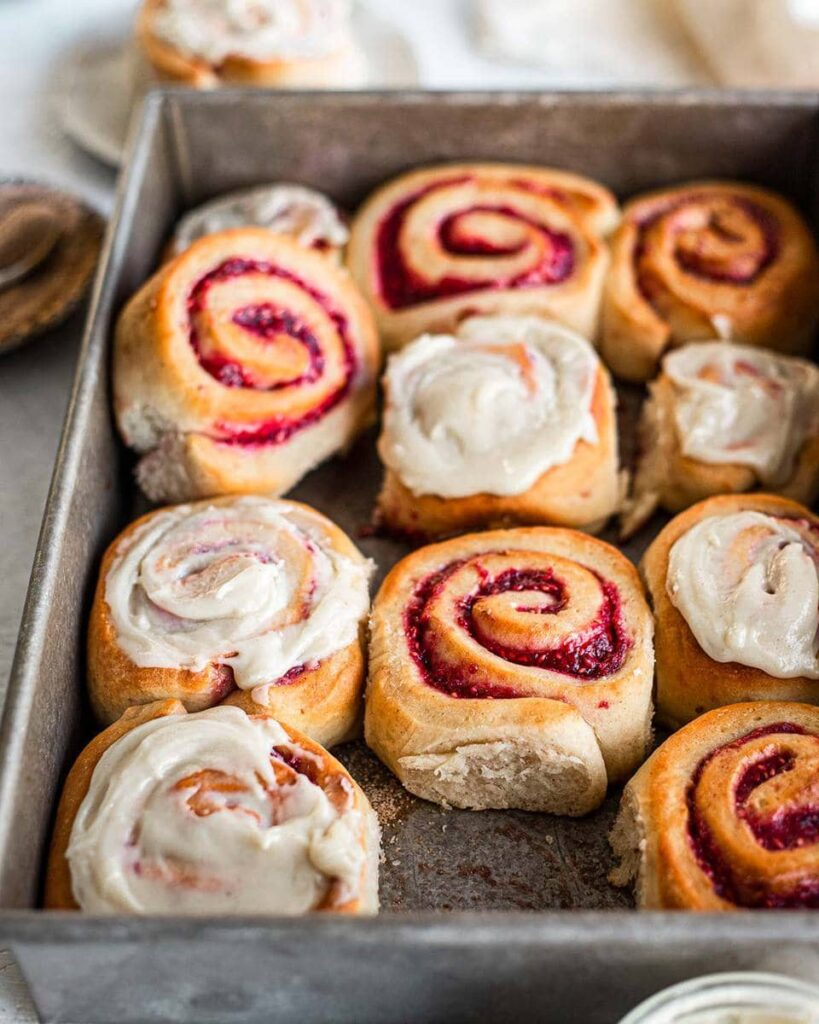 Jam Donut Cinnamon Rolls in baking tray. Some are iced and some are not. One roll is removed showing the feathery and soft edge of one of the rolls.