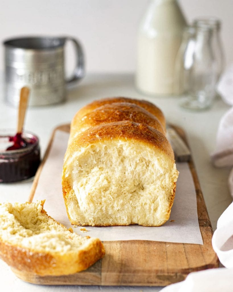Vegan brioche french bread on chopping board. Slice cut off showing golden and soft interior. The board is surrounded by brioche accompaniments such as jam