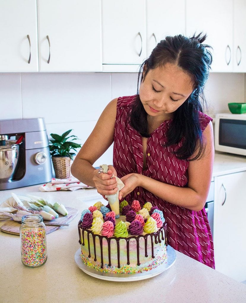 Author decorating a cake, demonstrating one of the many ways you can be paid as an Instagram food blogger