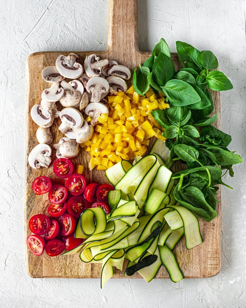 Vegetables for vegan pita pizzas on chopping board