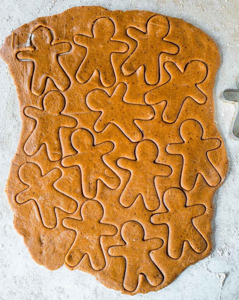 Flattened gingerbread dough and with gingerbread people shapes cut out