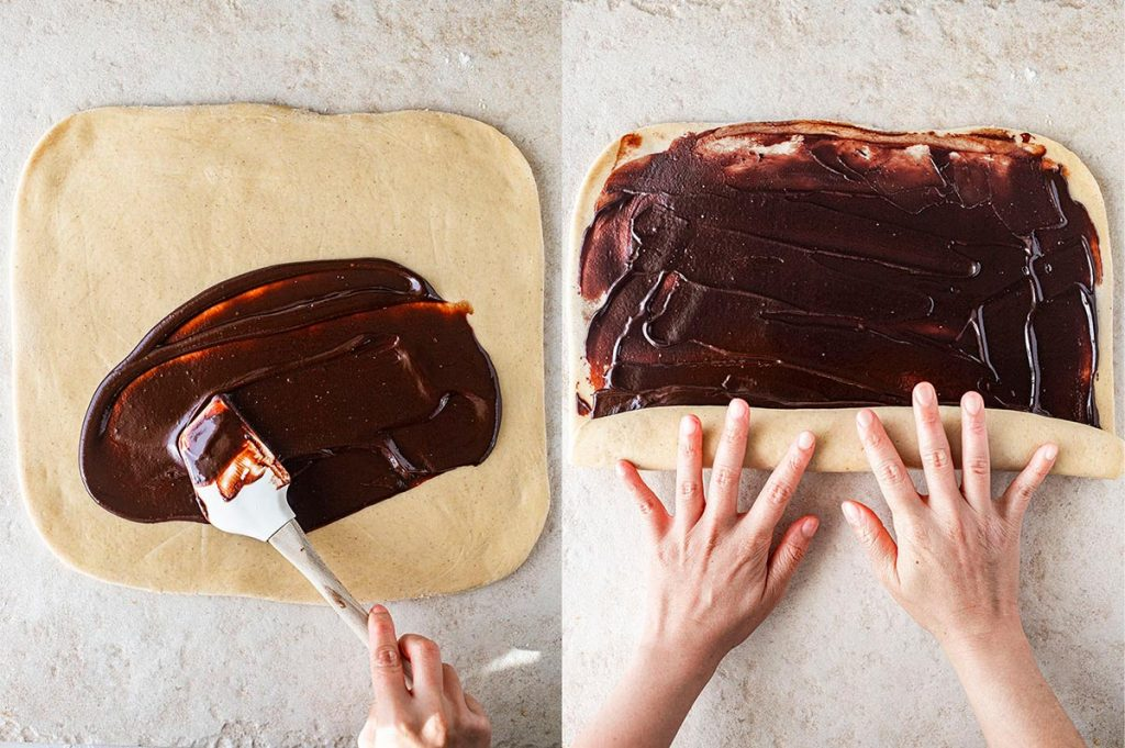Vegan chocolate babka: spreading the chocolate ganache on the dough and rolling it into a tube